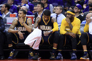 George Hill #3, Paul George #13 and Ty Lawson #10 of the Indiana Pacers look on from the bench late in the second half of Game Two against the Toronto Raptors of the Eastern Conference Quarterfinals during the 2016 NBA Playoffs at the Air Canada Centre on April 18, 2016 in Toronto, Ontario, Canada.  NOTE TO USER: User expressly acknowledges and agrees that, by downloading and or using this photograph, User is consenting to the terms and conditions of the Getty Images License Agreement.