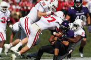 Kain Colter #2 of the Northwestern Wildcats is tackled by (L-R) Nick Mangieri #56, Mark Murphy #37 and Alexander Webb #27 of the Indiana Hoosiers at Ryan Field on September 29, 2012 in Evanston, Illinois. Northwestern defeated Indiana 44-29.