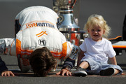 Dan Wheldon of England, driver of the #98 William Rast-Curb/Big Machine Dallara Honda kisses the yard of bricks alongside son, Sebastian Wheldon during the 95th Indianapolis 500 Mile Race Trophy Presentation at Indianapolis Motor Speedway on May 30, 2011 in Indianapolis, Indiana.