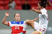 Heather O'Reilly of the USA struggles for the ball with Tang Jiali  of China during a match between USA and China as part of International Women's Football Tournament of Brasilia at Mane Garrincha Stadium on December 10, 2014 in Brasilia, Brazil.
