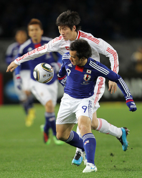 Shinji Okazaki of Japan and Peng Zhao of China compete for the ball during the East Asian Football Championship 2010 match between Japan and China at Ajinomoto Stadium on February 6, 2010 in Tokyo, Japan.