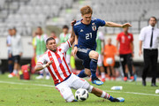 Gotoku Sakai of Japan is tackled by Richard Ortiz of Paraguay during the international friendly match between Japan and Paraguay at Tivoli Stadion on June 12, 2018 in Innsbruck, Austria.