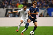 Yuya Osako of Japan and Diego Laxalt of Uruguay compete for the ball the international friendly match between Japan and Uruguay at Saitama Stadium on October 16, 2018 in Saitama, Japan.