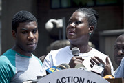 Trayvon Martin's mother Sybrina Fulton speaks at a podium as Trayvon Martin's brother Jahvaris Fulton (L) stands by during a rally honoring Trayvon Martin organized by the National Action Network outside One Police Plaza in Manhattan on July 20, 2013 in New York City.  Demonstrators have gathered in various cities across the country to protest the acquittal of neighborhood watchman George Zimmerman and press for his federal prosecution in the shooting death of teenager Trayvon Martin.