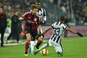 Alessio Cerci (L) of AC Milan is challenged by Patrice Evra (R) of Juventus FC during the Serie A match between Juventus FC and AC Milan at Juventus Arena on February 7, 2015 in Turin, Italy.