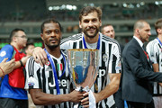 Fernando Llorente (R) and Patrice Evra of Juventus celebrates with the trophy after winning the Italian Super Cup final football match between Juventus and Lazio at Shanghai Stadium on August 8, 2015 in Shanghai, China.