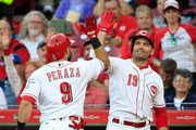 Jose Peraza #9 of the Cincinnati Reds celebrates with Joey Votto #19 after hitting a home run in the first inning against the Kansas City Royals at Great American Ball Park on September 26, 2018 in Cincinnati, Ohio.
