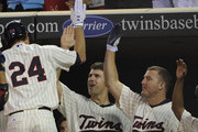 Joe Mauer #7 and Jim Thome #25 of the Minnesota Twins celebrate as Trevor Plouffe #24 of the Minnesota Twins returns to the dugout following a two-run home run against the Kansas City Royals in the fifth inning on July 14, 2011 at Target Field in Minneapolis, Minnesota.