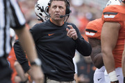 Head coach Mike Gundy of the Oklahoma State Cowboys checks the time clock during the first quarter of a NCAA college football game against the Kansas Jayhawks at the Boone Pickens Stadium on October 24, 2015 in Stillwater, Oklahoma.