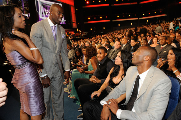 NFL player Terrell Owens (L) speaks with NBA player Kobe Bryant and wife