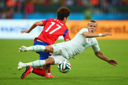 Djamel Mesbah of Algeria competes for the ball with Lee Chung-Yong of South Korea during the 2014 FIFA World Cup Brazil Group H match between South Korea and Algeria at Estadio Beira-Rio on June 22, 2014 in Porto Alegre, Brazil.