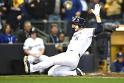Ryan Braun #8 of the Milwaukee Brewers scores a run off of a double hit by Jesus Aguilar #24 of the Milwaukee Brewers during the first inning in Game Six of the National League Championship Series at Miller Park on October 19, 2018 in Milwaukee, Wisconsin.
