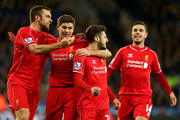 Adam Lallana (2nd R) of Liverpool celebrates with teammates after scoring a goal to level the scores at 1-1 during the Barclays Premier League match between Leicester City and Liverpool at The King Power Stadium on December 2, 2014 in Leicester, England.