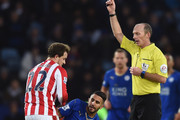 Xherdan Shaqiri (L) of Stoke City is shown a yellow card by referee Mike Dean (R) after fouling Riyad Mahrez (C) of Leicester City during the Barclays Premier League match between Leicester City and Stoke City at The King Power Stadium on January 23, 2016 in Leicester, England.