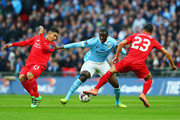 Yaya Toure of Manchester City goes between Roberto Firmino (L) and Emre Can of Liverpool (R) during the Capital One Cup Final match between Liverpool and Manchester City at Wembley Stadium on February 28, 2016 in London, England.