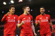 James Milner of Liverpool (C) celebrates with Roberto Firmino (R) and Emre Can (L) as he scores their first goal from a penalty during the Barclays Premier League match between Liverpool and Swansea City at Anfield on November 29, 2015 in Liverpool, England.