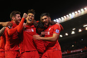 James Milner of Liverpool (2R) is congratulated by Adam Lallana (L), Roberto Firmino (2L), Emre Can (R) as he scores their first goal from a penalty during the Barclays Premier League match between Liverpool and Swansea City at Anfield on November 29, 2015 in Liverpool, England.