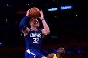 Blake Griffin #32 of the LA Clippers drives to the basket over Luol Deng #9 of the Los Angeles Lakers during the first half of the Los Angeles Lakers home opener at Staples Center on October 19, 2017 in Los Angeles, California.