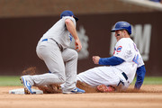 Logan Forsythe #11 of the Los Angeles Dodgers tags out Anthony Rizzo #44 of the Chicago Cubs during a stolen base attempt in the fourth inning at Wrigley Field on June 20, 2018 in Chicago, Illinois.