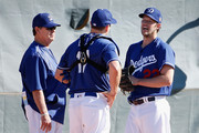 Starting pitcher Clayton Kershaw #22 of the Los Angeles Dodgers talks with pitching coach Rick Honeycutt and catcher A.J. Ellis #17 as they participate in a spring training workout at Camelback Ranch on February 20, 2016 in Glendale, Arizona.