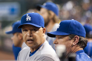 Manager Dave Roberts #30 of the Los Angeles Dodgers and pitching coach Rick Honeycutt #40 look on from the dugout of the MLB game against the Arizona Diamondbacks at Chase Field on September 18, 2016 in Phoenix, Arizona.