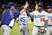 Yasiel Puig #66 of the Los Angeles Dodgers high fives pitching coach Rick Honeycutt after defeating the Arizona Diamondbacks in the MLB game at Chase Field on July 8, 2013 in Phoenix, Arizona. The Dodgers defeated the Diamondbacks 6-1.
