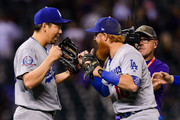 Kenta Maeda #18 of the Los Angeles Dodgers is congratulated by Justin Turner #10 after a save from a ninth inning appearance with a runner on and one out against the Colorado Rockies at Coors Field on September 7, 2018 in Denver, Colorado.