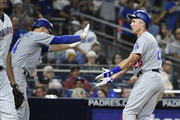 Chase Utley #26 of the Los Angeles Dodgers is congratulated by Enrique Hernandez #14 after scoring during the eighth inning of a baseball game against the San Diego Padres at PETCO Park on July 11, 2018 in San Diego, California.