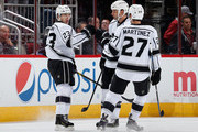 Dustin Brown #23 of the Los Angeles Kings celebrates with Robyn Regehr #44 and Alec Martinez #27 after Brown scored a first period goal against the Arizona Coyotes during the NHL game at Gila River Arena on December 4, 2014 in Glendale, Arizona.