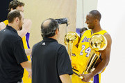 Kobe Bryant #24  of the Los Angeles Lakers reacts after receiving two NBA Finals Larry O'Brien Championship Trophy's from Lakers photographers Noah Graham (L) and Andrew D. Bernstein during a photo session with teammates Pau Gasol #16 and Derek Fisher #2 during Media Day at the Toyota Center on September 25, 2010 in El Segundo, California. NOTE TO USER: User expressly acknowledges and agrees that, by downloading and/or using this Photograph, user is consenting to the terms and conditions of the Getty Images License Agreement.