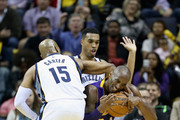 Kobe Bryant #24 of the Los Angeles Lakes tries to get away form the defense of Vince Carter #15 and Courtney Lee #5 of the Memphis Grizzlies during the game at FedExForum on November 11, 2014 in Memphis, Tennessee.