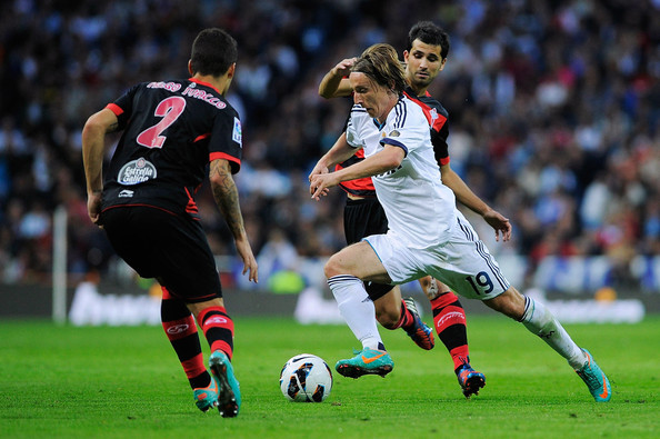 Luka Modric Luka Modric of Real Madrid CF competes for the ball with Alex lopez of RC Celta de Vigo during the La Liga match between Real Madrid CF and RC Deportivo La Coruna at Bernabeu on October 20, 2012 in Madrid, Spain.