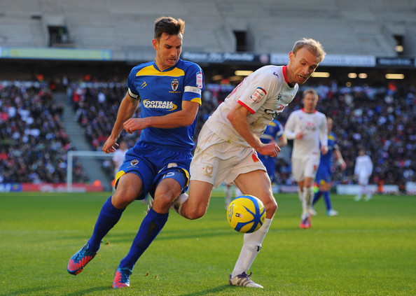 Luke Chadwick of MK Dons battles with Steve Gregory of AFC Wimbledon during the FA Cup with Budweiser Second Round match between MK Dons and AFC Wimbledon at StadiumMK on December 2, 2012 in Milton Keynes, England. This match is the first meeting between the two teams following the formation of AFC Wimbledon (the football club formed in 2002 by supporters unhappy with their club's relocation to Milton Keynes) and the MK Dons (which Wimbledon F.C. controversially became).