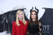 """Elle Fanning and Angelina Jolie attend a photocall for """"Maleficent: Mistress of Evil"""" at Mandarin Oriental Hotel on October 10, 2019 in London, England."""