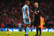 Vincent Kompany of Manchester City is spoken to by refeee Mike Dean during the Barclays Premier League match between Manchester City and Arsenal at Etihad Stadium on January 18, 2015 in Manchester, England.
