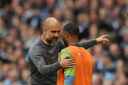 Josep Guardiola, Manager of Manchester City speaks to Raheem Sterling of Manchester City during the Premier League match between Manchester City and Burnley FC at Etihad Stadium on October 20, 2018 in Manchester, United Kingdom.
