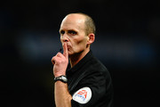 Referee Mike Dean gestures during the Barclays Premier League match between Manchester City and Chelsea at Etihad Stadium on February 3, 2014 in Manchester, England.
