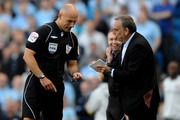 West Ham United Manager Avram Grant pretends to sign an autograph for Referee  Howard Webb after he dropped his notebook during the Barclays Premier League match between Manchester City and West Ham United at the City of Manchester Stadium on May 1, 2011 in Manchester, England.