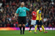 Rferee Mike Dean signals during the Barclays Premier League match between Manchester United and Arsenal at Old Trafford on May 17, 2015 in Manchester, England.