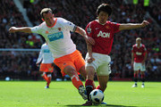 Park Ji-Sung of Manchester United is tackled by Charlie Adam of Blackpool during the Barclays Premier League match between Manchester United and Blackpool at Old Trafford on May 22, 2011 in Manchester, England.