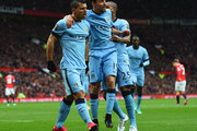 Sergio Aguero of Manchester City (L) celebrates with Jesus Navas (C) and Fernandinho (25) as he scores their first goal during the Barclays Premier League match between Manchester United and Manchester City at Old Trafford on April 12, 2015 in Manchester, England.