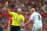 Referee Mike Dean shows a yellow card to Jonjo Shelvey of Swansea City during the Barclays Premier League match between Manchester United and Swansea City at Old Trafford on August 16, 2014 in Manchester, England.