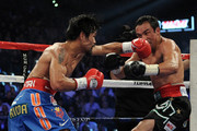(R-L) Manny Pacquiao connects with a left to the head of Juan Manuel Marquez during the WBO world welterweight title fight at the MGM Grand Garden Arena on November 12, 2011 in Las Vegas, Nevada.