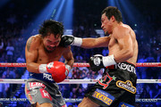 (R-L) Juan Manuel Marquez lands a right to the face of Manny Pacquiao during their welterweight bout at the MGM Grand Garden Arena on December 8, 2012 in Las Vegas, Nevada.