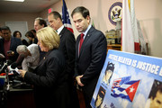 """Sen. Marco Rubio (R-FL) stands near a poster with pictures of those lost from the group called """"Brothers to the Rescue"""" when they were shot down by Cuban fighter jets in 1996, as he and other congressional people addressed the decision by President Barack Obama to change the United States Cuba policy on December 18, 2014 in Miami, Florida. Mr. Rubio was joined by Rep. Ileana Ros-Lehtinen (R-FL) (L) and Rep Mario Mario Diaz-Balart (R-FL) (C) as they held the press conference to denounce the  changes to U.S.-Cuba policy by the Obama administration."""