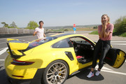 Porsche Brand Ambassadors Maria Sharapova and Mark Webber interact during a break of driving with the high performance sports car Porsche 911 RT2 RS on the Weissach race track before the start of the Porsche Tennis Grand Prix tennis tournament on April 20, 2018 in Stuttgart, Germany.