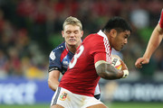 Manu Tuilagi of the Lions is tackled by Nic Henderson and Bryce Hegarty during the International Tour Match between the Melbourne Rebels and the British & Irish Lions at AAMI Park on June 25, 2013 in Melbourne, Australia.