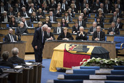 In this handout photo provided by the German Government Press Office (BPA),  Former Foreign Minister of the United States of America James Baker bows in front of the coffin as (L-R) President of the Bundestag Norbert Lammert, Chancellor Angela Merkel, Regional chairman of the Saxony CDU Stanislaw Tillich, President of the Constitutional Court Andreas Vosskuhle sit behind during the state memorial ceremony to honor Hans-Dietrich Genscher at World Congress Center on April 17, 2016 in Bonn, Germany. Genscher, a member of the German Free Democrats (FDP), served as German foreign minister from 1974 to 1992 and was widely respected as a shrewd and successful diplomat through the end of the Cold War era.
