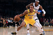 Avery Bradley #11 of the Los Angeles Lakers dribbles in front of Ja Morant #12 of the Memphis Grizzlies during the first quarter at Staples Center on February 21, 2020 in Los Angeles, California.  NOTE TO USER: User expressly acknowledges and agrees that, by downloading and or using this photograph, User is consenting to the terms and conditions of the Getty Images License Agreement.