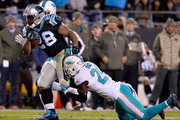 Reshad Jones #20 of the Miami Dolphins tackles Jonathan Stewart #28 of the Carolina Panthers during their game at Bank of America Stadium on November 13, 2017 in Charlotte, North Carolina.